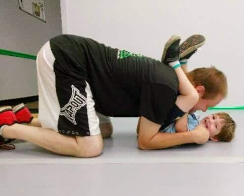 Adult play grappling with young boy